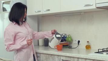 mulher despejando água quente de uma chaleira elétrica em um copo na cozinha de casa foto