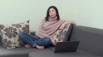 retrato mulher sentar no sofá olhar para câmera iniciar videoconferência, falar durante reunião virtual usar videochamada, conceito de tecnologia moderna foto