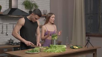 casal apaixonado de atletas gravando um vlog de comida de vídeo sobre culinária saudável na câmera do telefone na cozinha em casa. conceito de vlogging, educação e mídia social foto