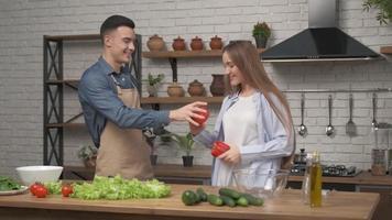 jovem casal feliz e ativo família dançando rindo juntos preparando comida em casa, despreocupado e alegre marido e mulher se divertindo cozinhando um jantar romântico e saudável, ouvir música na cozinha foto