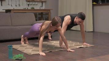 home fitness, conceito de treino. homem e mulher exercitando juntos no quarto em quarentena covid-19, vista lateral. casal de esportes fazendo exercícios de flexão em casa foto