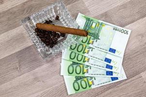 Notas de 100 euros e cinzeiro com charuto foto