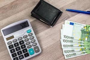 Notas de 100 euros, calculadora, potrafofli e caneta foto