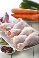 coxas de frango cru com legumes para cozinhar foto
