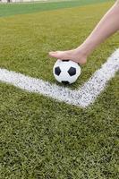 pé de menina na bola de futebol na manhã de campo verde foto