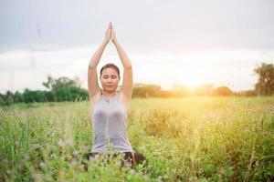 mulher linda ioga praticando ioga em prados. foto