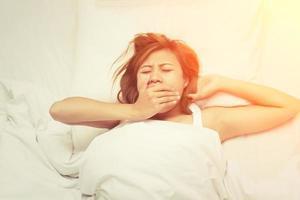 bela jovem com sono bocejando ao acordar de manhã foto