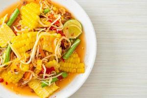 som tum - salada tailandesa de papaia apimentada com milho foto