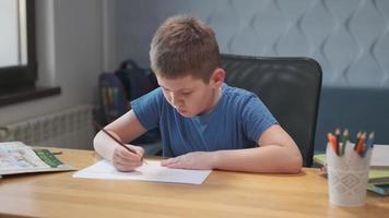 garotinho fofo desenha com lápis está envolvido com a criatividade em casa ou na escola foto