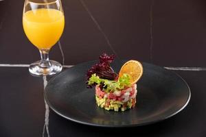 tártaro de atum fresco cru com close-up de especiarias em um prato e copo com suco. horizontal em fundo preto foto
