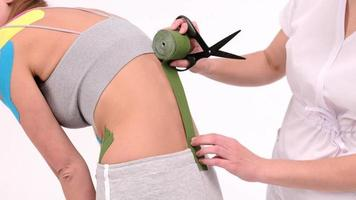 O cinesiologista mede o comprimento das fitas até o pescoço de uma paciente do sexo feminino, a recuperação de uma atleta após uma lesão, cinesiotapes na terapia da osteocondrose foto