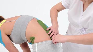 O fisioterapeuta cola fitas cinesiológicas nas costas da paciente, fita cinesiológica, terapia cinesiológica, atleta está se recuperando após lesão na região lombar. foto
