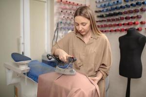 alfaiate femail usando vapor para engomar. o gerador de vapor. estilista passando tecido em seu estúdio foto