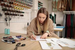estilista de moda feminina desenha esboços. jovem e atraente costureira desenhando em estúdio foto