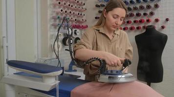 um estilista de moda no trabalho pairando roupas com ferro e vapor em uma oficina de costura. produção de roupas. produtos de costura no negócio do vestuário. foto