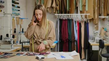 empresário de design de alfaiataria de roupas está olhando para amostras de tecido e falando no smartphone. ela está examinando o esboço com cuidado e pensando nas roupas do futuro. foto