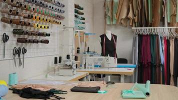 oficina de alfaiataria, alfaiataria de desgaste sob encomenda. interior do pequeno estúdio de moda. vista de rolos de tecido, carretéis de linha e padrões foto