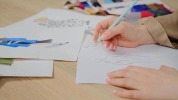 close-up do designer feminino usando lápis e folha de papel para esboços de moda. alfaiate mulher criando design de nova coleção de roupas. foto