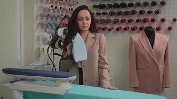 alfaiate feminina está passando roupas na tábua de passar com um vaporizador de ferro. ferro com vapor e jato de água. foto