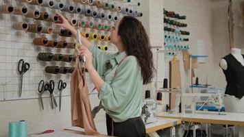 alfaiate femail concentrado escolhendo fios sob a cor do tecido na oficina. conceito de processo de trabalho criativo. foto