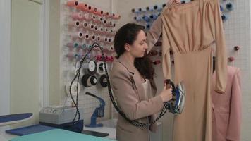 uma costureira prepara um novo vestido sob medida por um vaporizador de ferro especializado em um ateliê de costura. o processo de costura de roupas novas. foto
