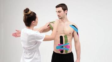 o médico cola uma fita de tratamento especial no ombro da cota de malha. fisioterapeuta cola fitas cinesiológicas no ombro do paciente, fitas cinesiológicas, terapia cinesiológica, atleta se recuperando após lesão de lombos, 4k foto