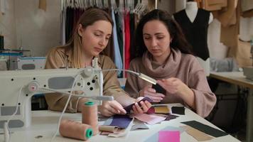 dois estilistas femail olhando amostras de esboços em um estúdio de costura. dois alfaiates ou costureiras trabalhando com máquinas de costura e amostras de tecido foto