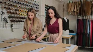 duas costureiras trabalhando com um pano e giz sobre uma mesa. costureira usa giz no contorno do padrão em tecido, no ateliê. alfaiate profissional, designer de moda no estúdio de costura. foto