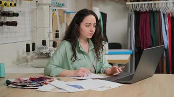designer de moda competente criando novos esboços no laptop. alfaiate femail sentado no ateliê do ateliê. foto