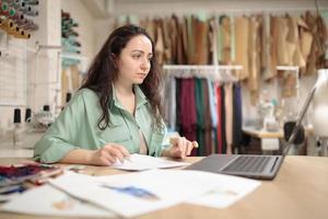 o estilista olha com entusiasmo para o laptop enquanto trabalha com esboços no ateliê do estúdio. Pequenos negócios foto