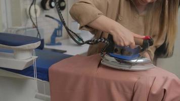 costureira passa a vapor uma jaqueta usando um ferro antigo. a mão de uma mulher segura o ferro e alisa a jaqueta. foto