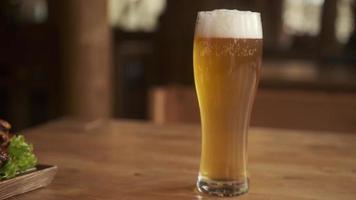vista do close up de cerveja e lanches. um copo com cerveja e petiscos em um prato na mesa de madeira. o garçom coloca um prato de batatas fritas, croutons, frango e molho foto