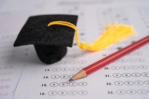 chapéu e lápis de lacuna de formatura na folha de respostas foto