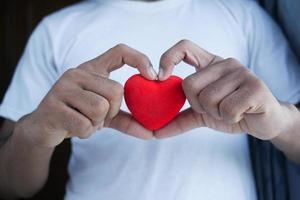 homem segurando um coração vermelho sobre fundo azul foto