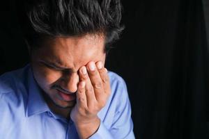 close-up de um homem chateado sofrendo de fortes dores nos olhos foto