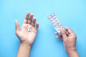 a mão do homem com comprimidos médicos e blister em azul foto