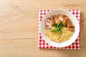 Tigela de macarrão com perna de porco estufada seca - comida asiática foto