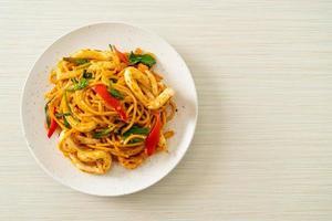 espaguete frito com ovo salgado e lula - comida de fusão foto
