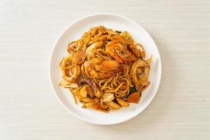 espaguete seco com frutos do mar frito tom yum - estilo de comida de fusão foto