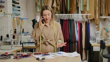 designer de moda profissional está falando ao telefone celular e visualizando um esboço de roupas em um estúdio de alfaiataria. trabalho diário e comunicação no conceito de local de trabalho. foto