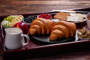delicioso café da manhã com croissants frescos e frutas vermelhas maduras foto