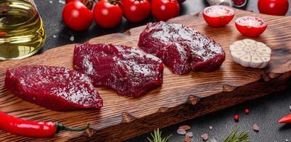 bife mignon de carne crua fresca, com sal, pimenta, tomilho, tomate foto