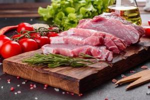 Pedaços de carne de porco prontos para cozinhar em um fundo escuro na cozinha foto