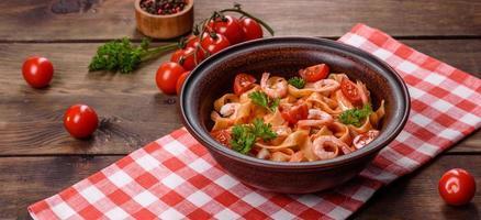 macarrão fettuccine com camarão, tomate cereja, molho, especiarias e ervas foto