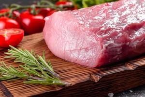 Pedaços frescos de carne de porco pronta para cozinhar em um fundo escuro foto