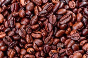 grãos de café torrado fresco, close-up contra um fundo escuro foto