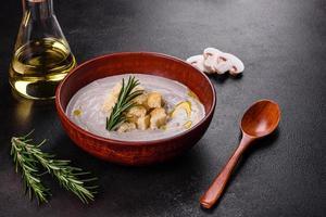 deliciosa e linda sopa de cogumelos em um prato marrom com uma colher de pau foto