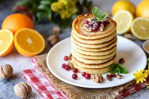 deliciosas e frescas lindas panquecas com mel cítrico e geléia foto