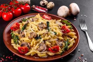 macarrão com cogumelos, queijo, espinafre, rukkola e tomate cereja foto