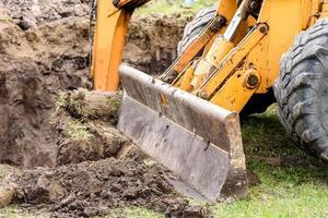 a escavadeira moderna realiza trabalhos de escavação no canteiro de obras foto